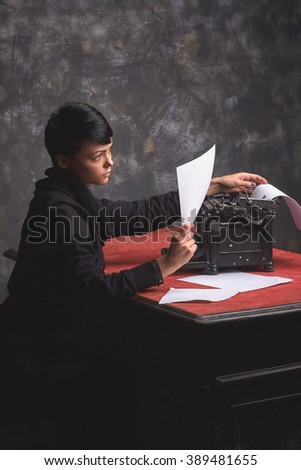 Young  beautiful woman writer in dark wear, creative process, reading her work, retro typewriter in art space with dark background - stock photo