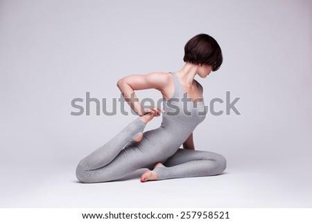 young beautiful woman yoga posing on a gray studio background - stock photo