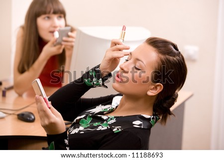 young beautiful women applying make-up at office - stock photo