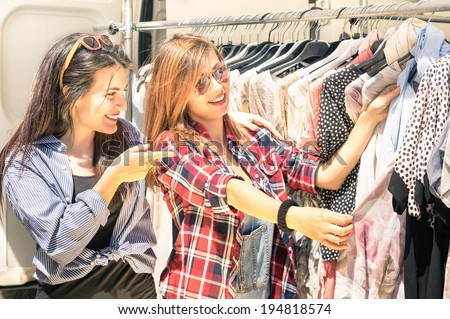 Young beautiful women at the weekly cloth market - Best friends sharing free time having fun and shopping in the old town in a sunny day