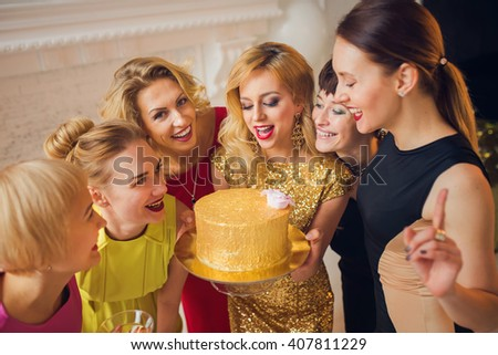 Young beautiful women celebrating birthday party. Pretty woman in gold dress presenting a birthday cake to her friends