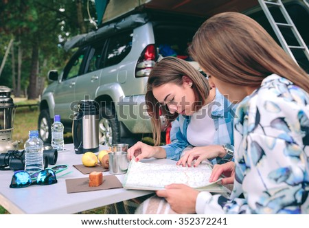 Young beautiful women friends looking road map in a campsite.Female friendship and leisure time concept. - stock photo
