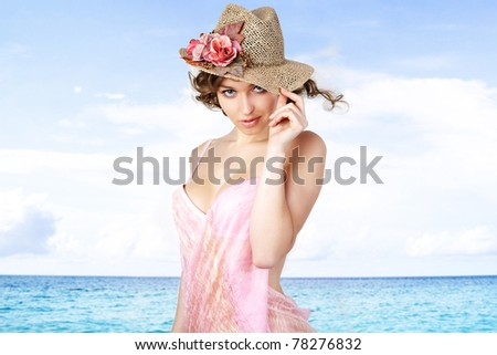 Young beautiful women in the pink  pareos and hat on the sunny tropical beach near sea. - stock photo