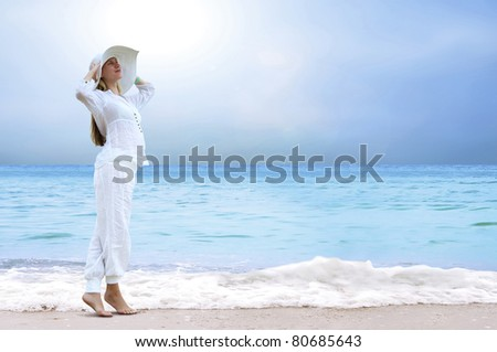 Young beautiful women in the white on the beach - stock photo