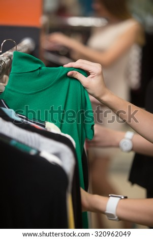 Young beautiful women shopping in fashion mall, choosing new clothes, looking through hangers with different casual colorful garments, picking up cute green turtleneck top, close up of hands - stock photo