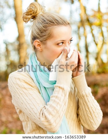 Young beautiful women suffering from influenza, blowing her nose. - stock photo