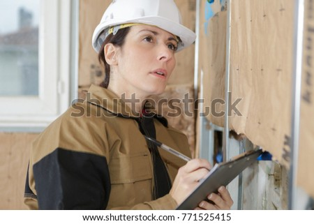young beautiful worker inspecting construction site