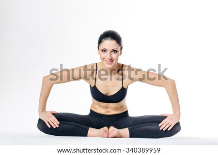 young beautiful yoga female posing on a studio background - stock photo