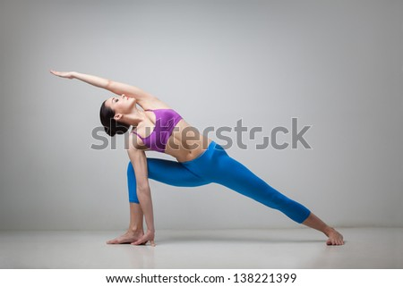 young beautiful yoga posing Utthita Parsvakonasana on a gray studio background - stock photo