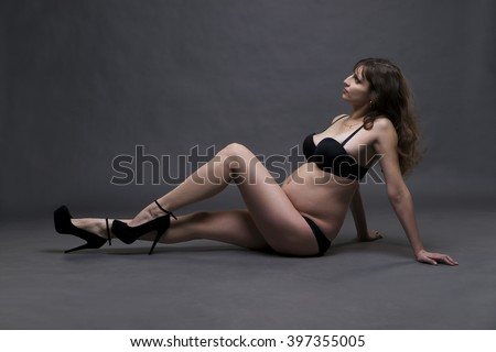 Young beauty and sexy caucasian pregnant woman in black lingerie on gray studio background