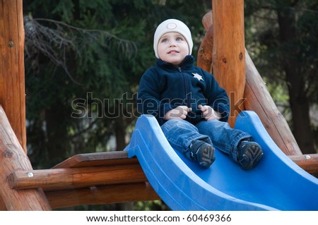 Young beauty boy is playing on the playground