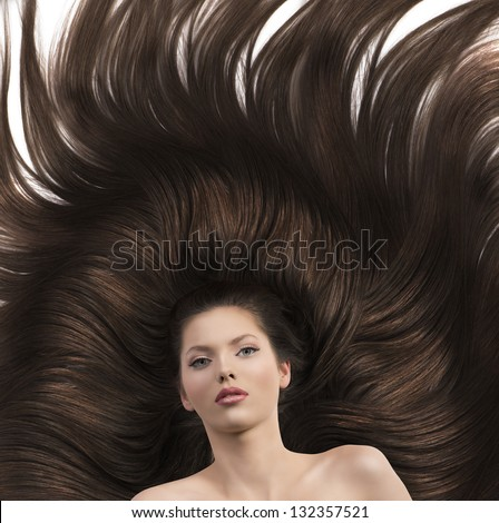 young beauty brunette with incredible long hair laying and looking - stock photo