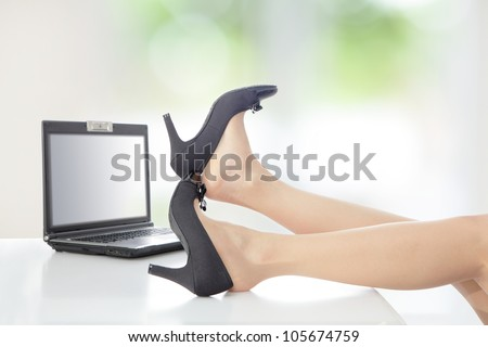 Young Beauty business woman take off her high heels shoes at company office with white table, window outside are green background - stock photo