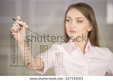 Young beauty businesswoman drawing a graph on glass screen in office. - stock photo