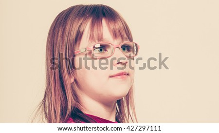 Young beauty charming girl wearing glasses. Portrait of lovely adorable female child in straight hair. - stock photo
