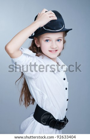 Young beauty girl in black hat with blue eyes posing at the studio