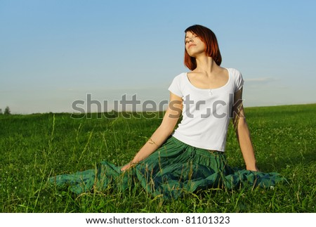 young beauty girl in long skirt sitting on summer lawn, eyes closed, relax concept
