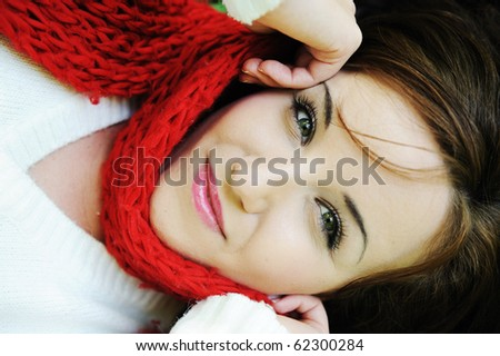 Young beauty girl laying on autumn ground and leaves, perfect face and natural skin, fashionable fall clothes, red shawl/scarf