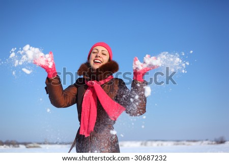 young beauty girl outdoor in winter throws snow