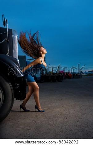 Young beauty girl posing near steel truck - stock photo