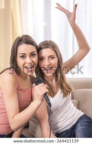 Young beauty girls sing  a song at home. And looking at camera. - stock photo