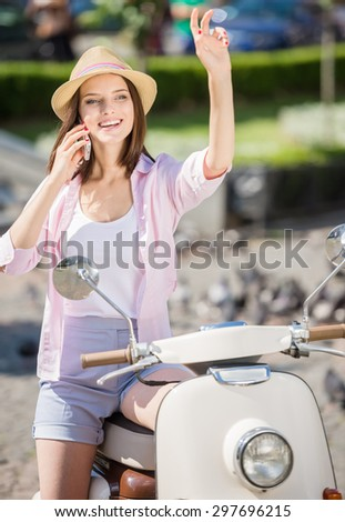 Young beauty in nifty hat sitting on scooter and smiling. - stock photo