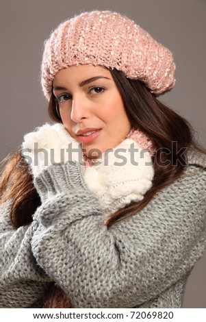 Young beauty keeping warm in winter woolly clothes