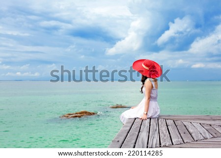 Young beauty lady with red hat sit on the pier look over sea and blue sky - stock photo