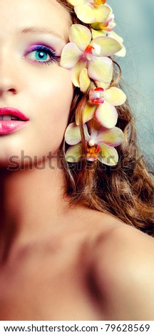 Young beauty portrait with orchid flowers