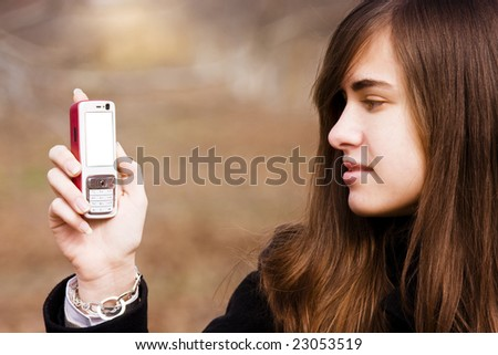 Young beauty showing cell phone with blank screen. - stock photo