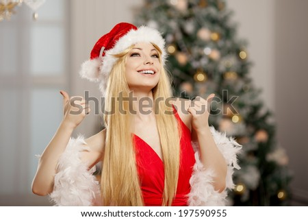 Young beauty smiling santa woman near the Christmas tree. Fashionable luxury girl celebrating New Year. Beautiful luxury trendy blonde. Thumb up - stock photo