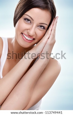 Young beauty - smiling woman, isolated on blue background - stock photo