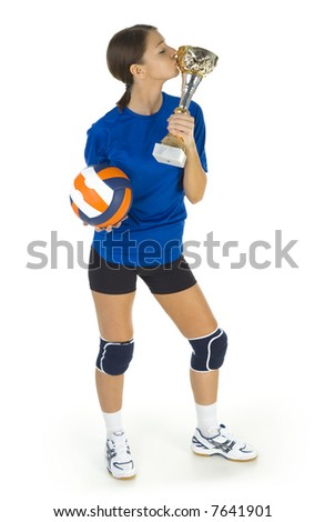 Young, beauty volleyball player. Holding ball and cup in hands. Kissing the cup. White background. Whole body, front view - stock photo
