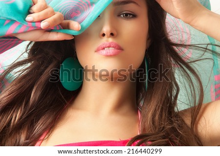 young beauty with blue scarf over her head, studio shot - stock photo