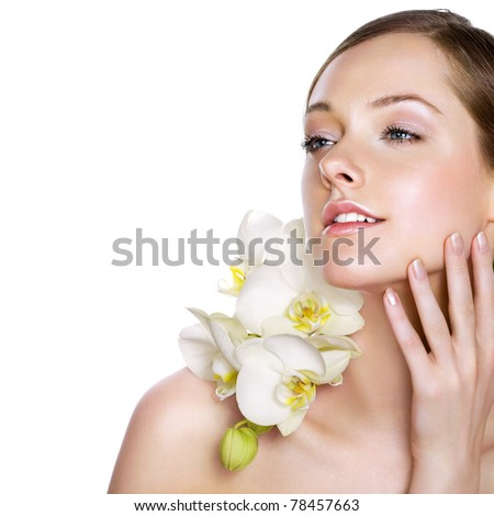 Young beauty with fresh white orchids. Space for text. - stock photo