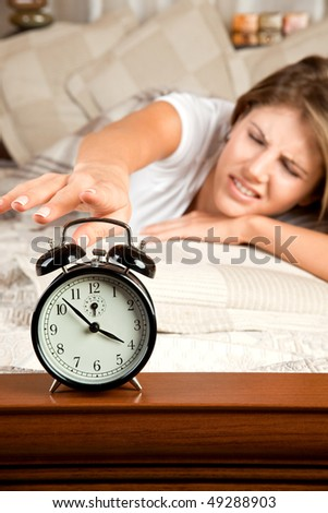 Young beauty woman couch in the bed and turning off the alarm clock