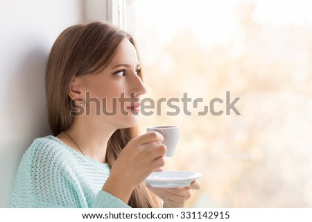Young beauty woman drinking coffee in a cafe outdoor. Elegant caucasian girl enjoying her latte in the morning