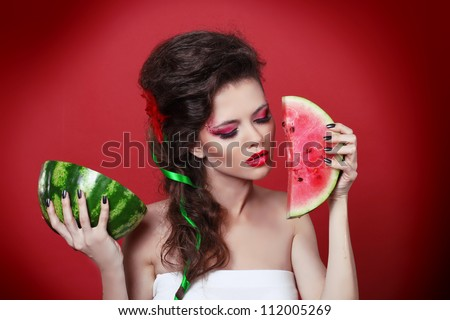 Young beauty woman holding watermelon in her hand over red background - stock photo