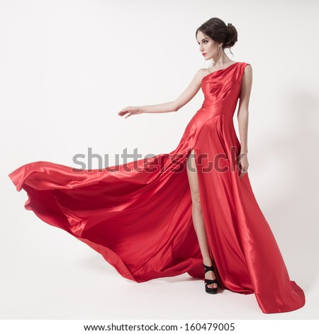Young beauty woman in fluttering red dress. White background. - stock photo