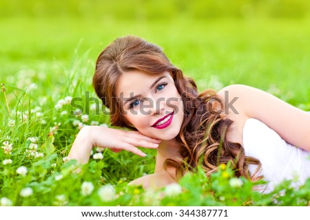 Young beauty woman lying on the grass in the park and smiling