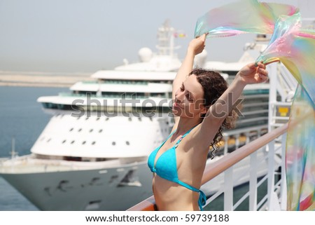 young beauty woman standing on cruise liner deck in bikini and holding pareo, half body - stock photo
