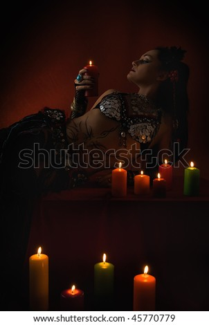 young beauty woman tribal dancer in dark red room - stock photo