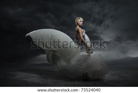 Young beauty woman wearing gorgeous dress standing over dark sky background