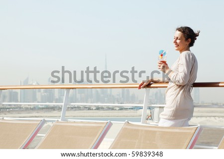 young beauty woman with cocktail standing on cruise liner deck, half body - stock photo
