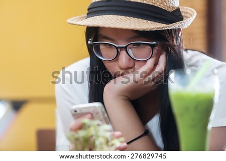 Young beauty woman writing message on cell phone in a cafe. Looking down  - stock photo