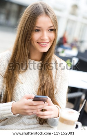 Young beauty woman writing message on cell phone in a street cafe. Looking away - stock photo