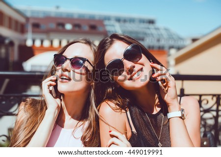 young beauty women, pretty sisters, girlfriends, together, call phone, using smartphone, sunglasses, fashion model, outdoor portrait, street photo, cute, holding, cell, cellular  - stock photo
