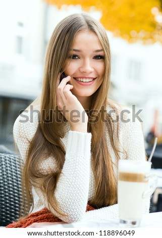 Young beauty women sitting in a street cafe with latte macchiato and talking on the cellphone - stock photo