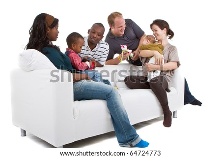 Young befriended multiracial families sitting on the couch and playing with their kids. - stock photo