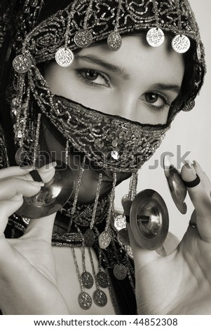 Young belly dancer with hand cymbals - stock photo